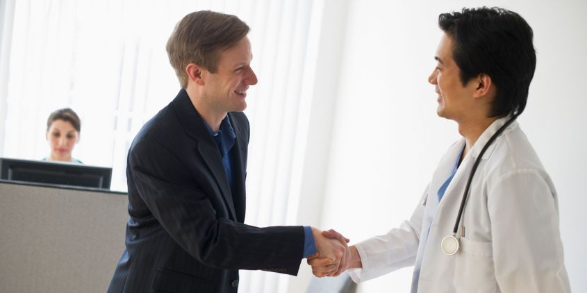 Salesman and doctor shaking hands. Image shot 2010. Exact date unknown.