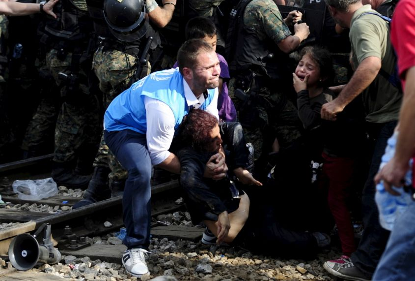 A woman collapses at the border line dividing Macedonia and Greece